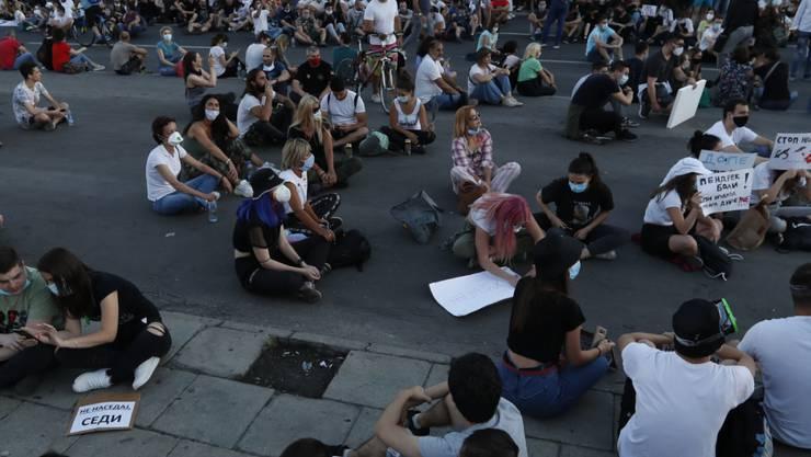 Demonstranten in Belgrad protestieren sitzend gegen die von Präsident Aleksandar Vucic verhängten Corona-Restriktionen. (Foto: Darko Vojinovic/AP/KEYSTONE-SDA)