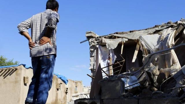 Ein Kurde schaut auf die Ruinen seines Hauses