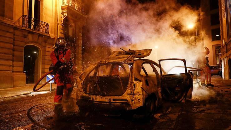 Feuerwehrmänner löschen ein brennendes Auto in der Nähe der Champs-Elysées. Nach dem 1:0-Sieg des FC Bayern gegen Paris Saint-Germain im Endspiel der Champions League in Lissabon ist es am Sonntagabend in der französischen Hauptstadt zu Ausschreitungen gekommen. Foto: Sameer Al-Doumy/AFP/dpa