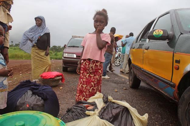 Ein Mädchen wartet vor der Grenze Sierra Leones.