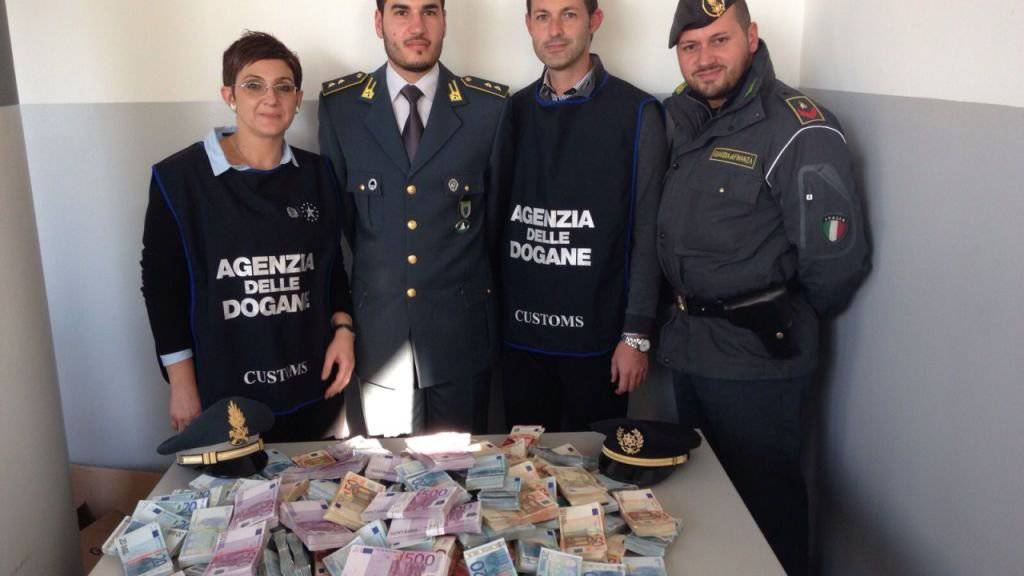 Fetter Geldschmuggel aufgedeckt: Italienisches Grenzpersonal hinter dem beschlagnahmten Geld.