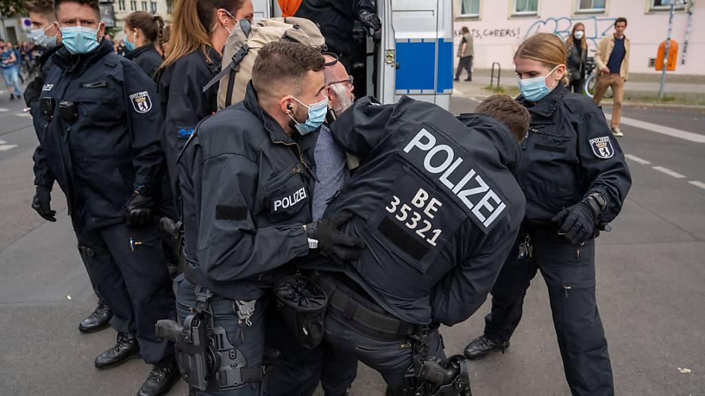 Polizisten halten an einem Polizeiwagen einen Teilnehmer der Demonstration fest, die aus Protest gegen die Corona-Politik veranstaltet wird. Foto: Christophe Gateau/dpa