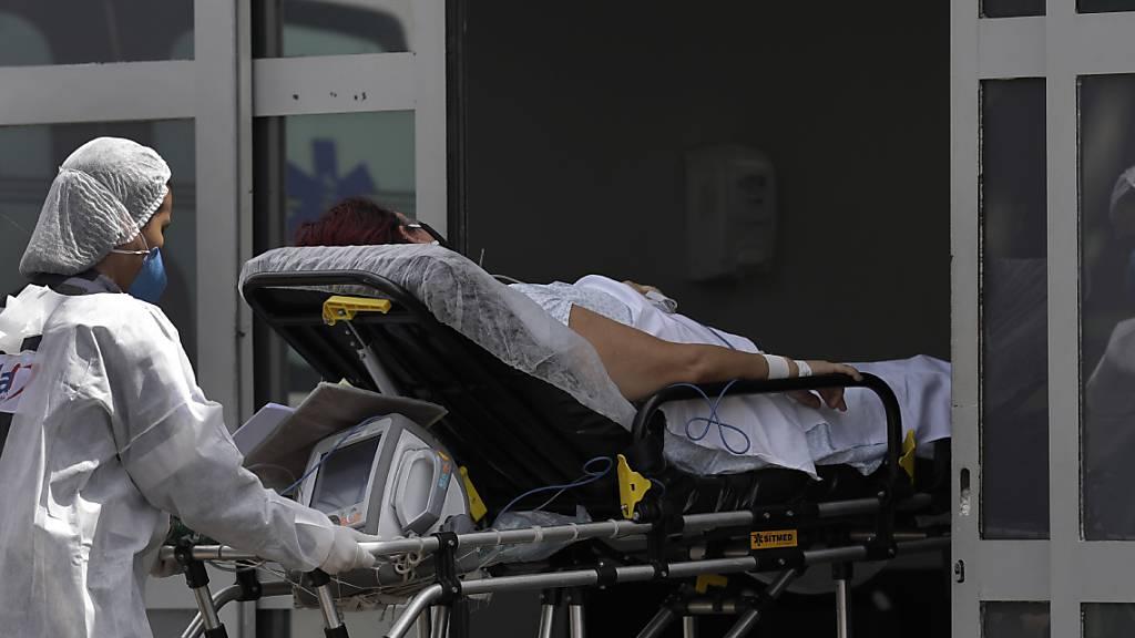 Ein Mitarbeiter des Gesundheitswesens schiebt einen Patienten mit Verdacht auf Covid-19 aus einem Krankenwagen in das öffentliche Krankenhaus HRAN in Brasilia. Foto: Eraldo Peres/AP/dpa