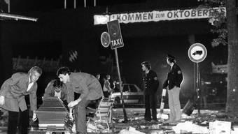 Ein Sarg wird am 26.09.1980 vom verwüsteten Tatort beim Oktoberfest in München (Bayern) weggetragen.