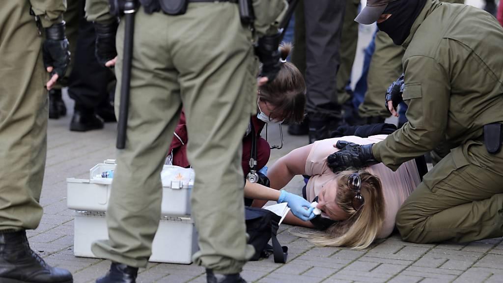 Eine Notärztin kümmert sich am Rande einer Demonstration gegen die Wahlergebnisse in Belarus um eine verletzte Frau, die neben Polizeibeamten auf dem Boden liegt. Foto: Uncredited/TUT.by/dpa
