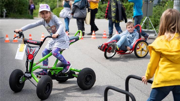 Kinder vergnügen sich vor der Ludothek Wettingen auf Fahrzeugen.