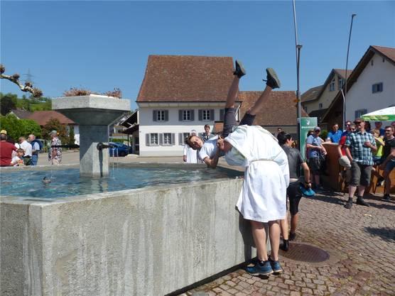 Nicht ganz freiwillig: ein Bad im Dorfbrunnen.