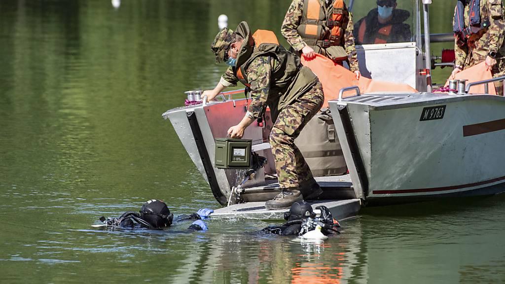 Polizeitaucher übergeben der Schweizer Armee die geborgenen Handgranaten im Rotsee.