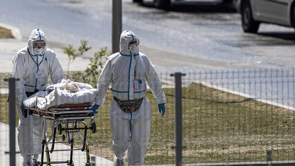 ARCHIV - Medizinische Mitarbeiter transportieren einen Patienten mit Verdacht auf Covid-19 auf dem Gelände eines Krankenhauses bei Moskau. Foto: Alexander Zemlianichenko/AP/dpa