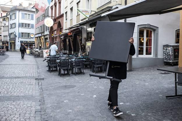 Eine Kellnerin räumt Restauranttische in Zürich von der Strasse.