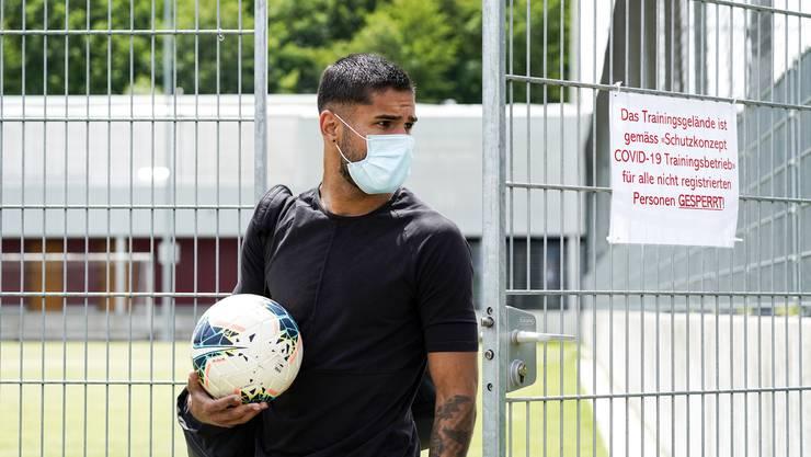 Miguel Peralta trifft mit Mundschutz und Ball auf dem FCA-Trainingsgelände ein.