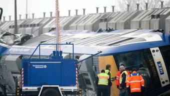 Polizisten und Rettungskräfte untersuchen den Zug