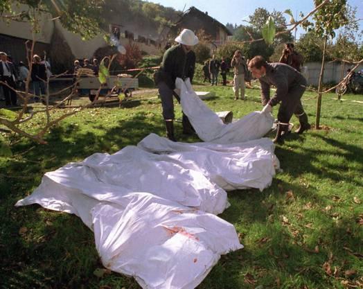 Leichensäcke vor dem Gehöft in Cheiry im Kanton Freiburg, wo 23 Sektenmitglieder ums Leben kamen. Bild: Keystone