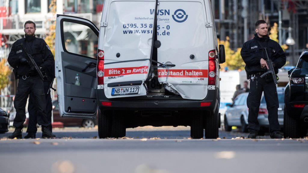 Polizisten mit Maschinenpistolen sichern in Berlin den  Geldtransporter mit aufgebrochenen Türen.