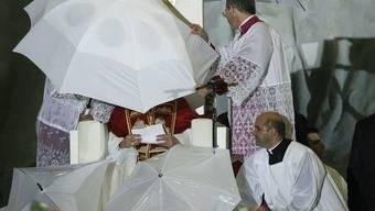 Hinter diesen Regenschirmen ist das Kirchenoberhaupt versteckt: Ein Gewitter unterbricht die päpstliche Ansprache in Madrid