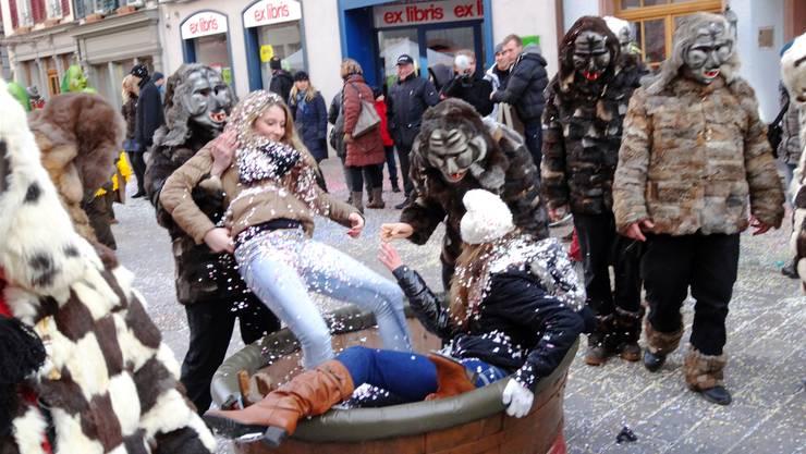 Umstrittene Aktion: Zuschauerinnen werden in Rheinfelden von Fasnächtlern im Konfetti-Zuber gebadet. ach (Archiv)