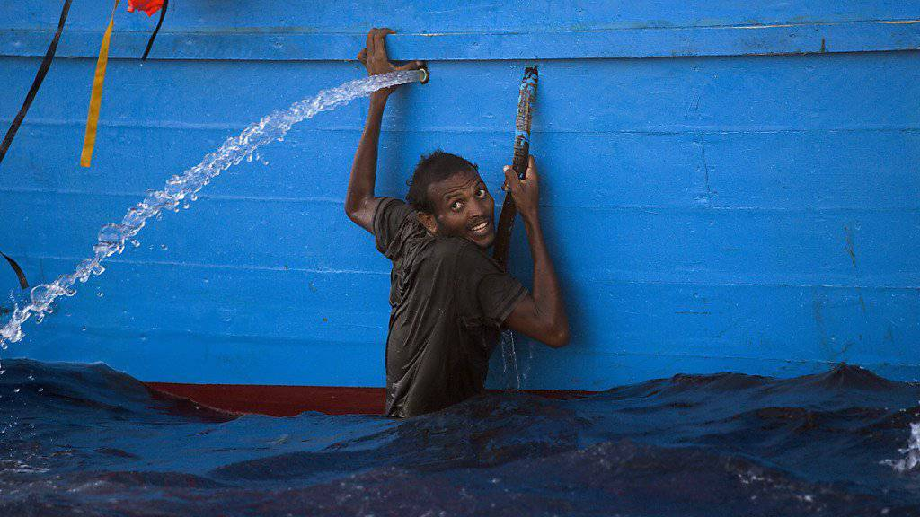 Ein Mann klammer sich an ein Boot im Meer vor Libyen, wo die italienische Küstenwache rund 6500 Flüchtlinge aus Seenot rettete.