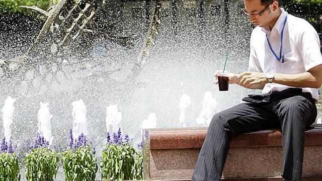 Temperaturen von weit über 30 Grad: Ein Japaner sitzt in Tokio nahe eines Brunnens