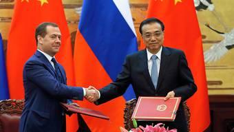 Der chinesische Ministerpräsident Li Lequiang (r.) und sein russischer Amtskollege Dmitri Medwedew vereinbaren eine Ausweitung des Handelsaustauschs ihrer Länder.