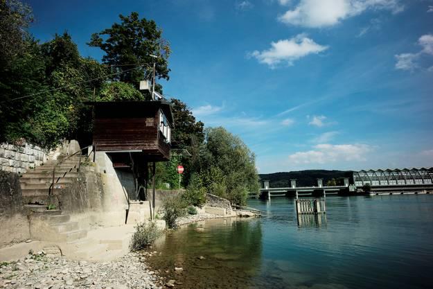 Am Rhein stehen erhöht Fischerhäuschen mit ihren Galgen und Holzsperren im seichten Wasser.