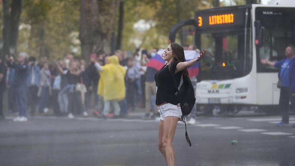 Eine Demonstrantin gestikuliert in Richtung der Polizei während einer Demonstration gegen die Corona-Impfungen und weiteren Maßnahmen zur Eindämmung der Corona-Pandemie. Foto: Petr David Josek/AP/dpa