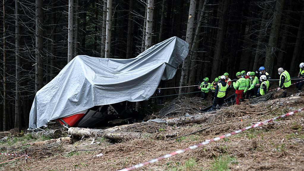 Einsatzkräfte des Bergrettungsdienstes arbeiten nach dem Absturz einer Seilbahngondel in Norditalien an der Unfallstelle. Die Justiz ermittelt in der Zwischenzeit gegen 14 Menschen.