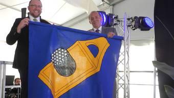 Gemeindeammann Urs Bosisio (rechts) übergibt Generalmanager Horst Beck demonstrativ eine Hägglinger Fahne.
