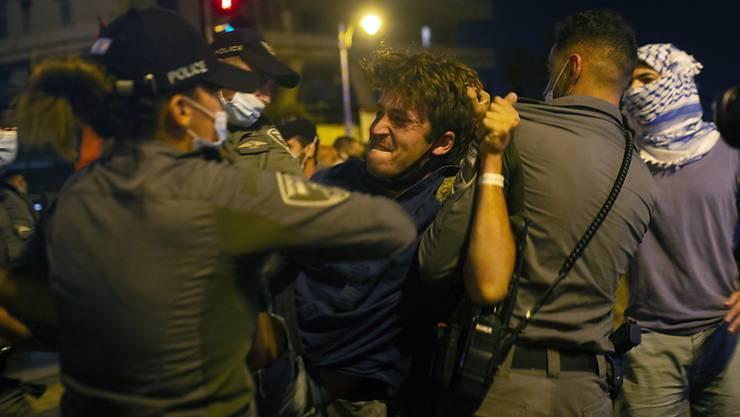 Polizisten nehmen einen Demonstranten während eines Protests vor der Residenz des israelischen Premierminister Netanjahu in Gewahrsam. Foto: Maya Alleruzzo/AP/dpa