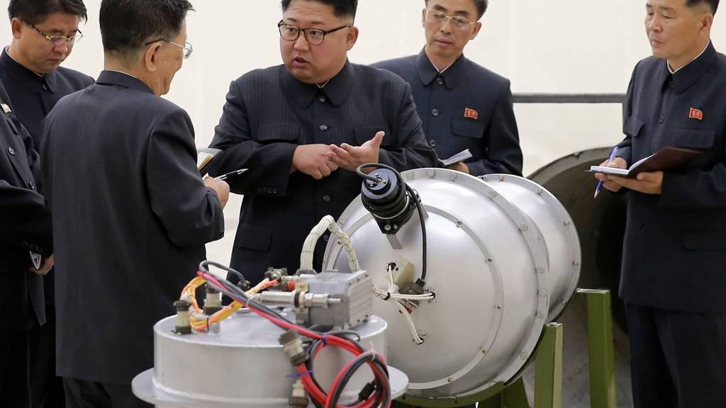 Der koreanische Machthaber Kim Jong-un mit begutachtet eine vermeintliche in Nordkorea hergestellte Bombe.