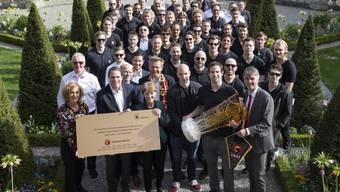 Gemeinderatsmitglieder und SCB posieren im Garten des Berner Erlacherhofs mit dem Meisterpokal.