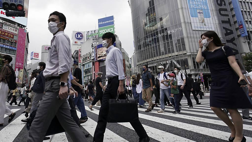 Passanten überqueren eine Straße in dem Stadtbezirk Shibuya. Japans Hauptstadt bestätigte am 31. Juli einen Zuwachs an mehr als 400 Corona-Neuinfektionen. Foto: Eugene Hoshiko/AP/dpa