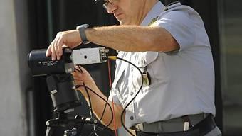 Ein Polizist bereitet die Kamera vor, die Steuerbetrüger blitzt (Archiv)