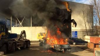 Mit Hilfe eines Baggers brachten die Angestellten die Fahrzeuge ins Freie.