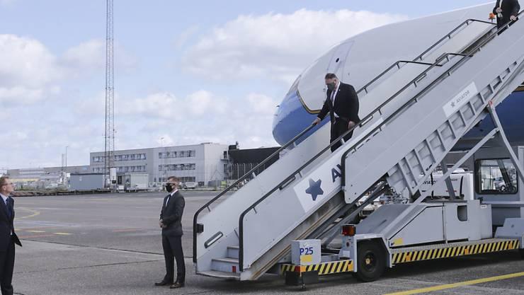 Mike Pompeo, Außenminister der USA, trägt einen Mund-Nasenschutz, während er nach seiner Landung aus der Maschine steigt und von Carla Sands (l), US-Botschafterin in Dänemark, begrüßt wird. Foto: Thibault Savary/pool AFP/AP/dpa