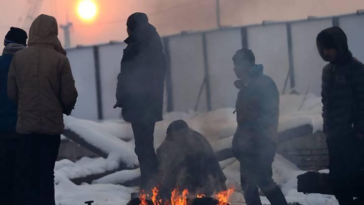 In Serbien gestrandete Flüchtlinge versuchen sich in der Kälte mit einem Feuer warm zu halten.