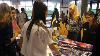 Schülerinnen diskutieren mit Bekleidungsgestalterinnen.