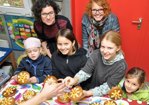 Kinder auf dem Spielplatz Güggi verzieren gemeinsam mit Mitgliedern von Soroptimist Club Solothurn Lebkuchen, die an Firmen der Region gehen.