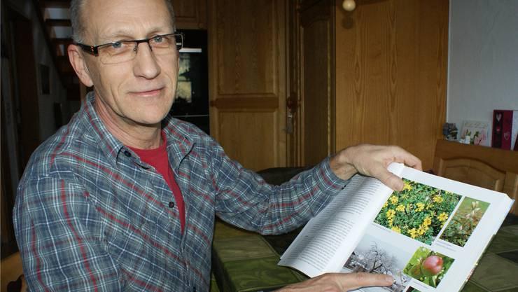 Amandus Brogle macht sich stark für den Erhalt des «Helliker Apfels» und deutet auf eine Abhandlung in der Dorfchronik von 2009. ach