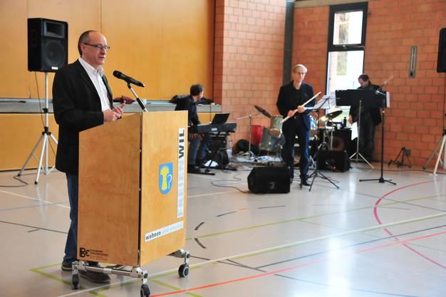Gemeinderat Daniel Aeschbach führte durch die Veranstaltung. Im Hintergrund die WWF-Band mit Albert Kasper an der Querflöte.