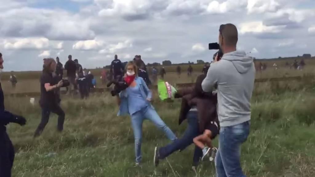 Kamerafrau stellt Flüchtling das Bein.
