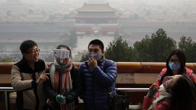 Peking-Besucher schützen sich mit Masken vor dem Smog. Foto: Keystone