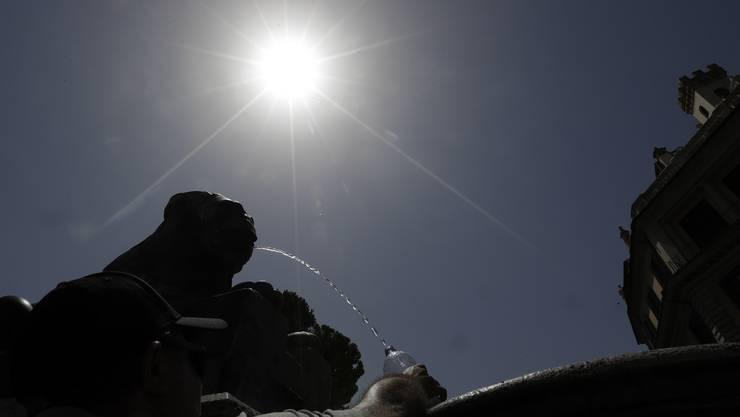 Ein Mann füllt eine Flasche mit Wasser an einem Brunnen in Rom. Die aktuelle Hitzewelle macht Italien zu schaffen.