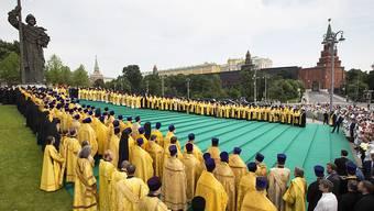 Die Taufe der Rus: Orthodoxe Priester an einer Zeremonie vor einer Statue von Fürst Wladimir in Moskau.