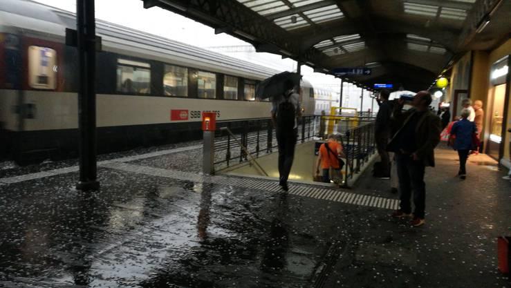 Hagelkörner fliegen auf das Perron am Gleis 1. Passanten spannen trotz Dach den Regenschirm auf, um nicht von Hagel-Querschlägern, die am Zug abprallen, getroffen zu werden.