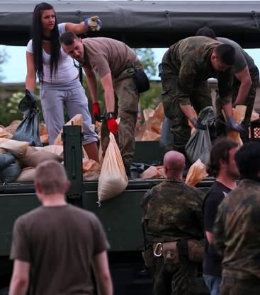 Soldaten helfen mit: Sie füllen in Rothensee bei Magdeburg Sandsäcke.