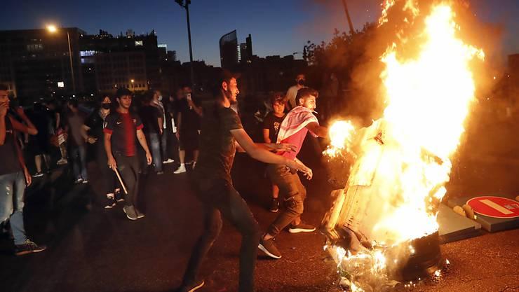 dpatopbilder - Demonstranten verbrennen bei einem Protest gegen die politische Elite Gegenstände, um eine Straße zu blockieren. Foto: Hussein Malla/AP/dpa