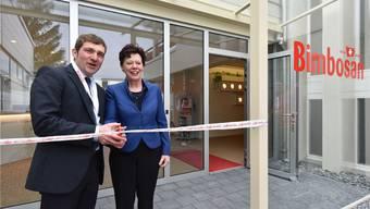 Bimbosan-CEO Daniel Bärlocher zerschneidet zusammen mit Regierungsrätin Esther Gassler das Band im Eingangsbereich des Firmengebäudes.