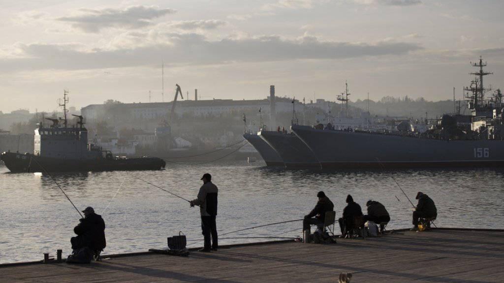 Lokale Fischer vor russischen Militärschiffen im Hafen von Sewastopol auf der Halbinsel Krim. Die NATO hatte ihre praktische Zusammenarbeit mit Russland in Folge der Krim-Annektion im März 2014 ausgesetzt. Nun soll der Dialog wiederbelebt werden. (Archiv)