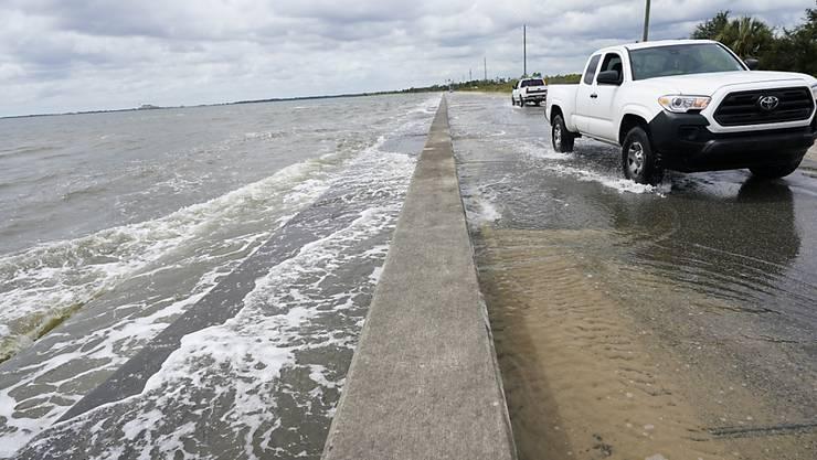 Ein Auto fährt über eine Straße, die durch den Tropensturm mit Meerwasser überflutet ist. Hurrikan «Sally» hat auf seinem Weg in Richtung der US-Golfküste weiter an Kraft gewonnen. Foto: Gerald Herbrt/AP/dpa - ACHTUNG: Nur zur redaktionellen Verwendung und nur mit vollständiger Nennung des vorstehenden Credits