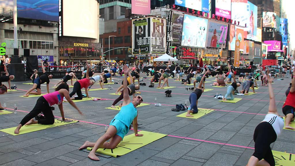 Menschen nehmen an einer gemeinsamen Yoga-Stunde inmitten des Times Square teil. Foto: Christina Horsten/dpa